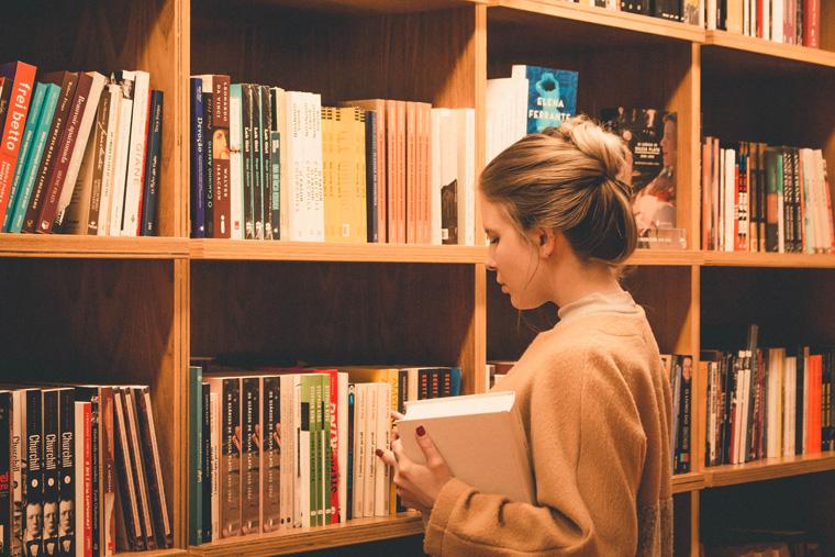 本屋で本を選んでいる金髪の外国人女性
