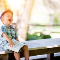 ベンチで本を読みながら笑っている男の子