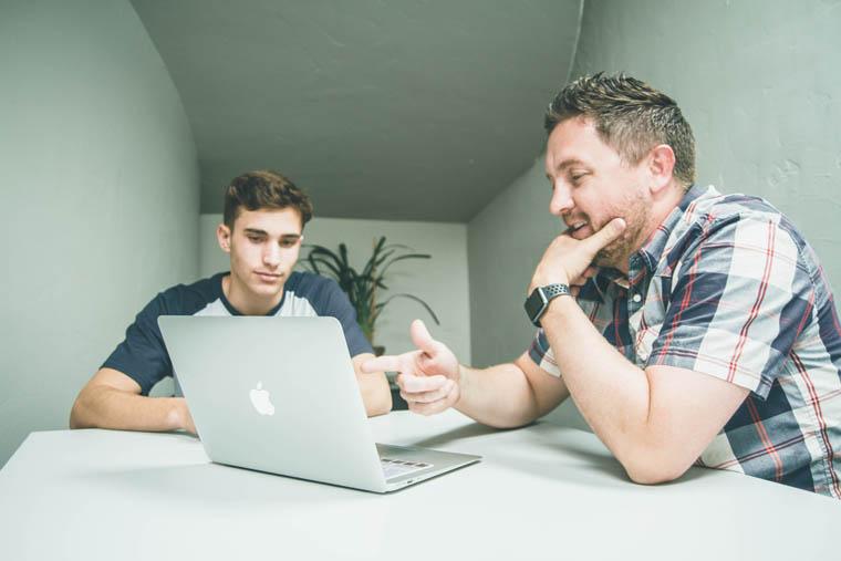 パソコンを見ながら相談している二人の男性