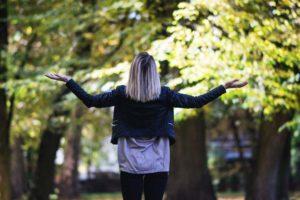 公園の中で両手を広げている後ろ姿の女性