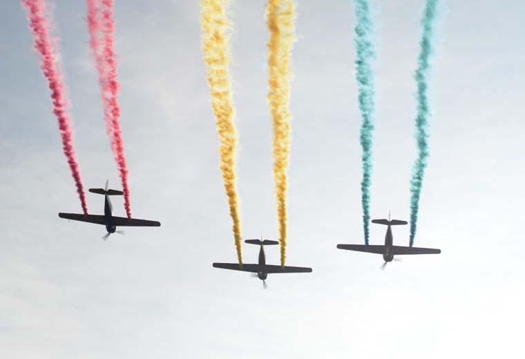 煙の色が違う3台の飛んでいる飛行機