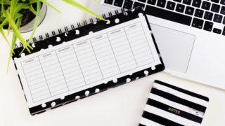 白い机の上に置かれたカレンダーとPCとノートと観葉植物
