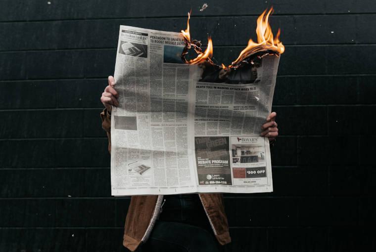 燃えている新聞を読んでいる男性