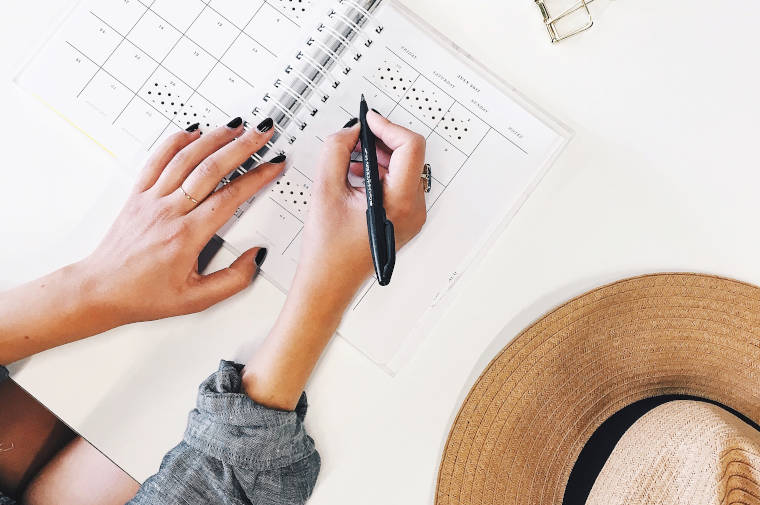 手帳に文字を記入している女性の手