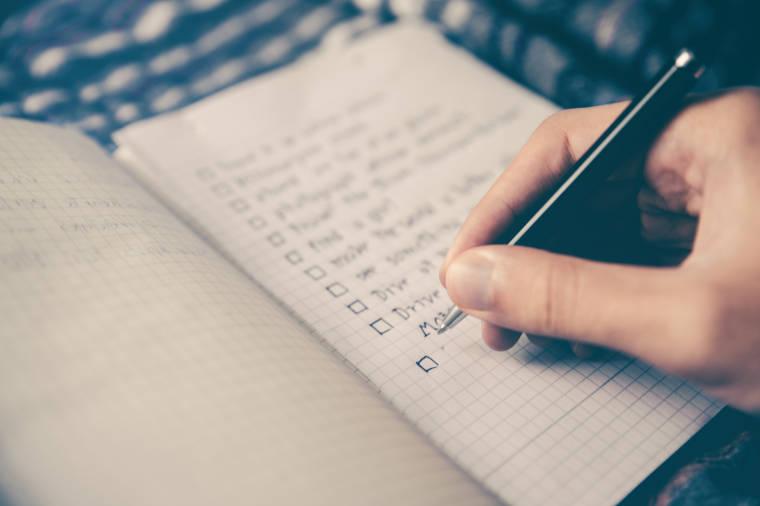 ペンを持ってノートにチェックリストを作っている人の手元