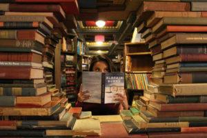 積み上げられた本の中で口元を隠している女性
