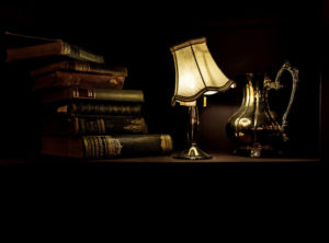 テーブルライトに照らされている積み上げられた本