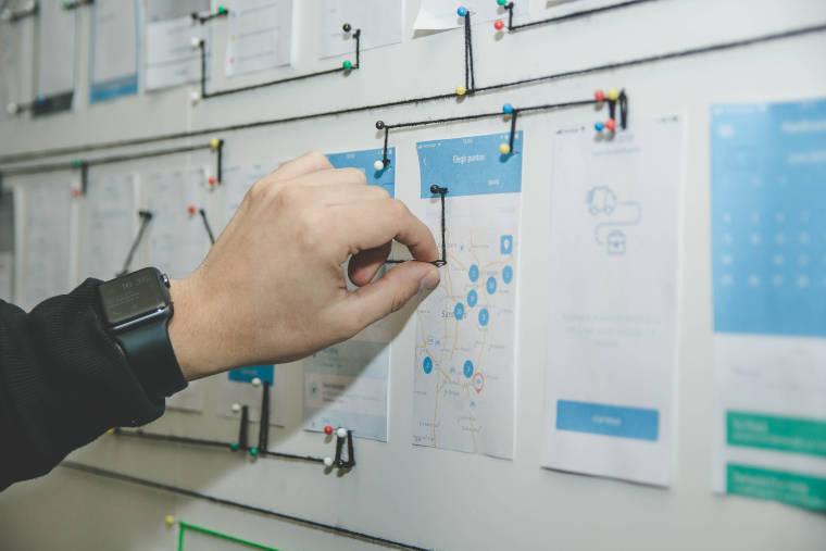 壁に貼り付けられた紙にピンを指している男性の手