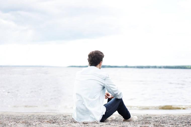 浜辺で体育座りをしている男性