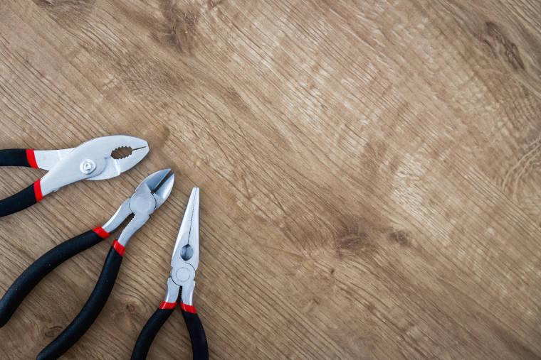 ペンチやニッパーが木の机に置かれている