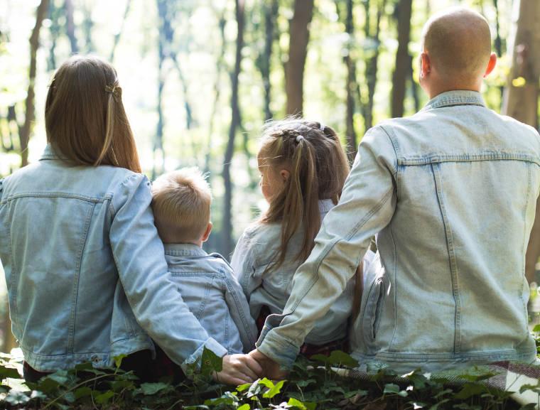 木々に腰かけている4人家族