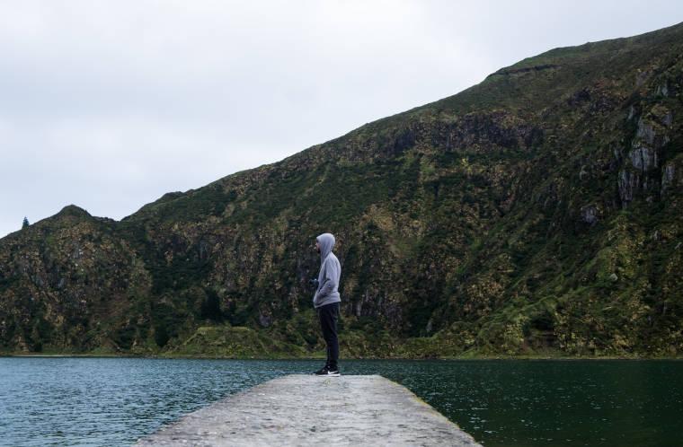 堤防で立って湖を見ている男性