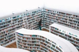 本棚から本を選ぶ男性
