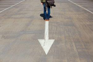 地面に書かれた矢印の逆側に立っている男性