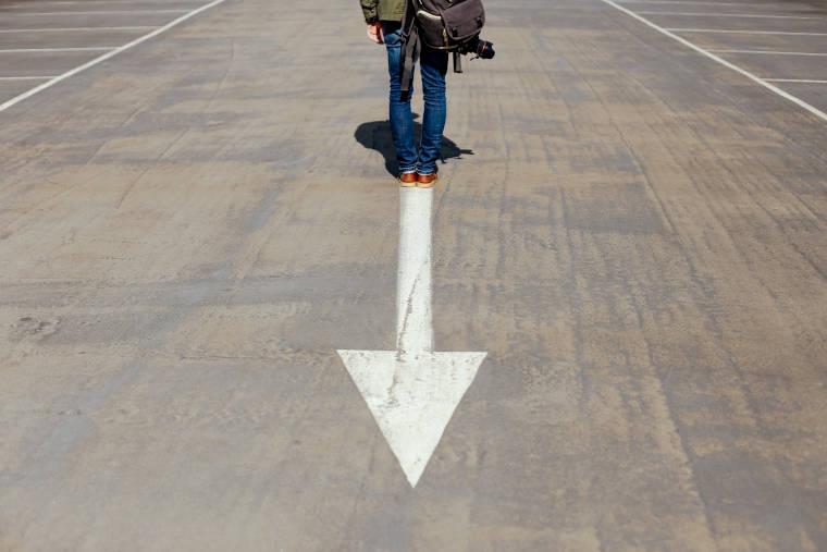 地面に書かれた矢印の上に立っている男性