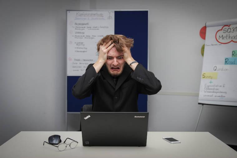 パソコンの画面を見て頭を抱えているスーツ姿の男性