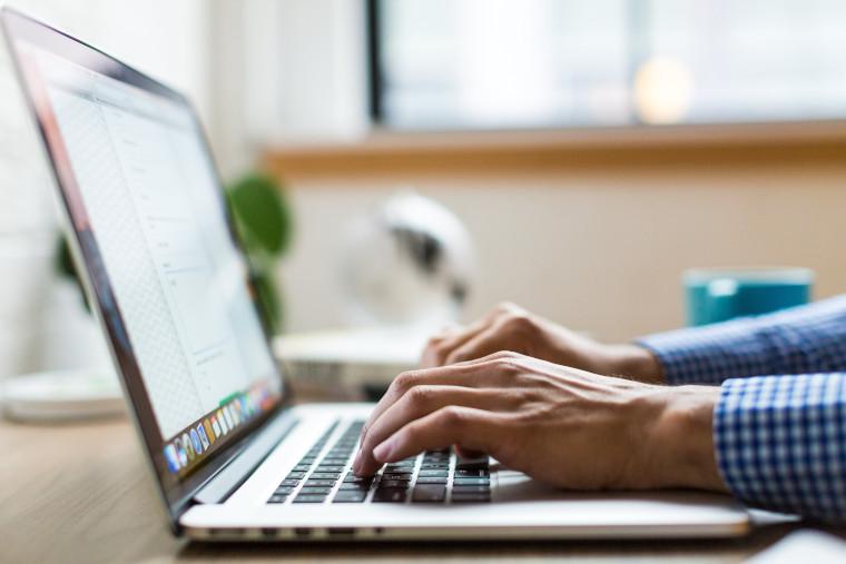 ノートパソコンでタイピングしている男性