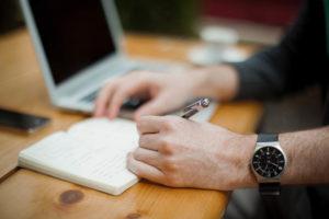 ノートに書きとりをしている男性の手元