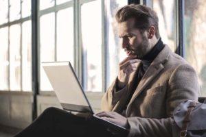 ノートパソコンを見ながら考え事をしている男性